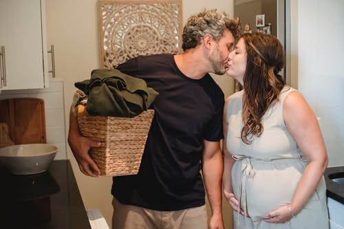 Happy adult man with laundry basket in hand kissing pregnant wife with closed eyes while standing together in bathroom