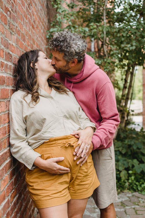 Romantic pregnant couple kissing in yard in daytime