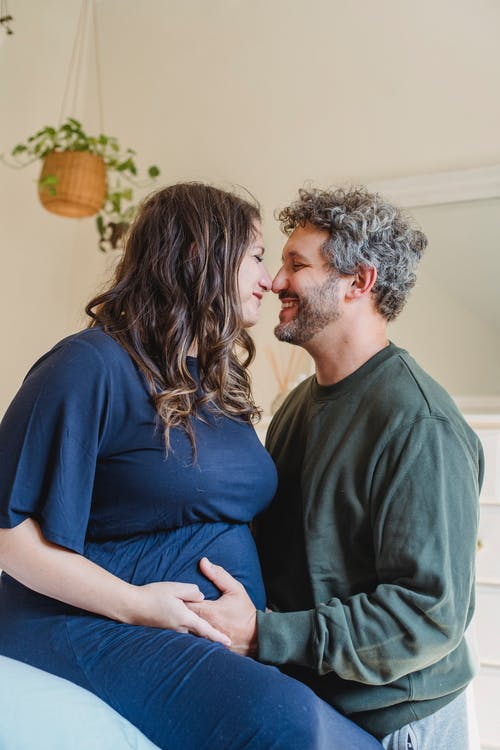 Enamored pregnant couple embracing in bedroom in daylight