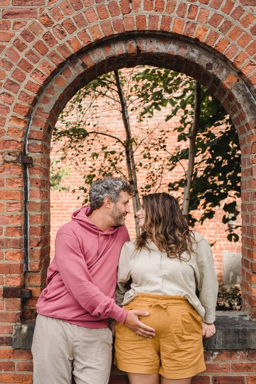 Stylish adult man in casual clothes touching tummy of pregnant wife while standing together near brick house and looking at each other