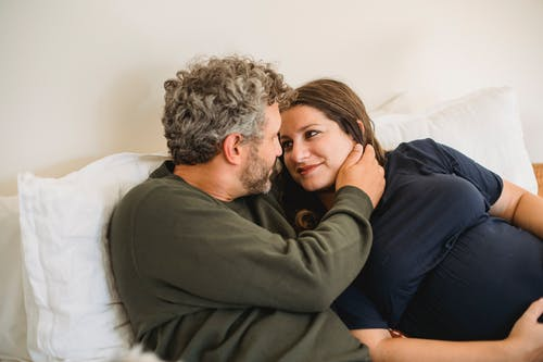 Enamored adult man in casual clothes lying on bed and touching face of happy pregnant wife during weekend at home