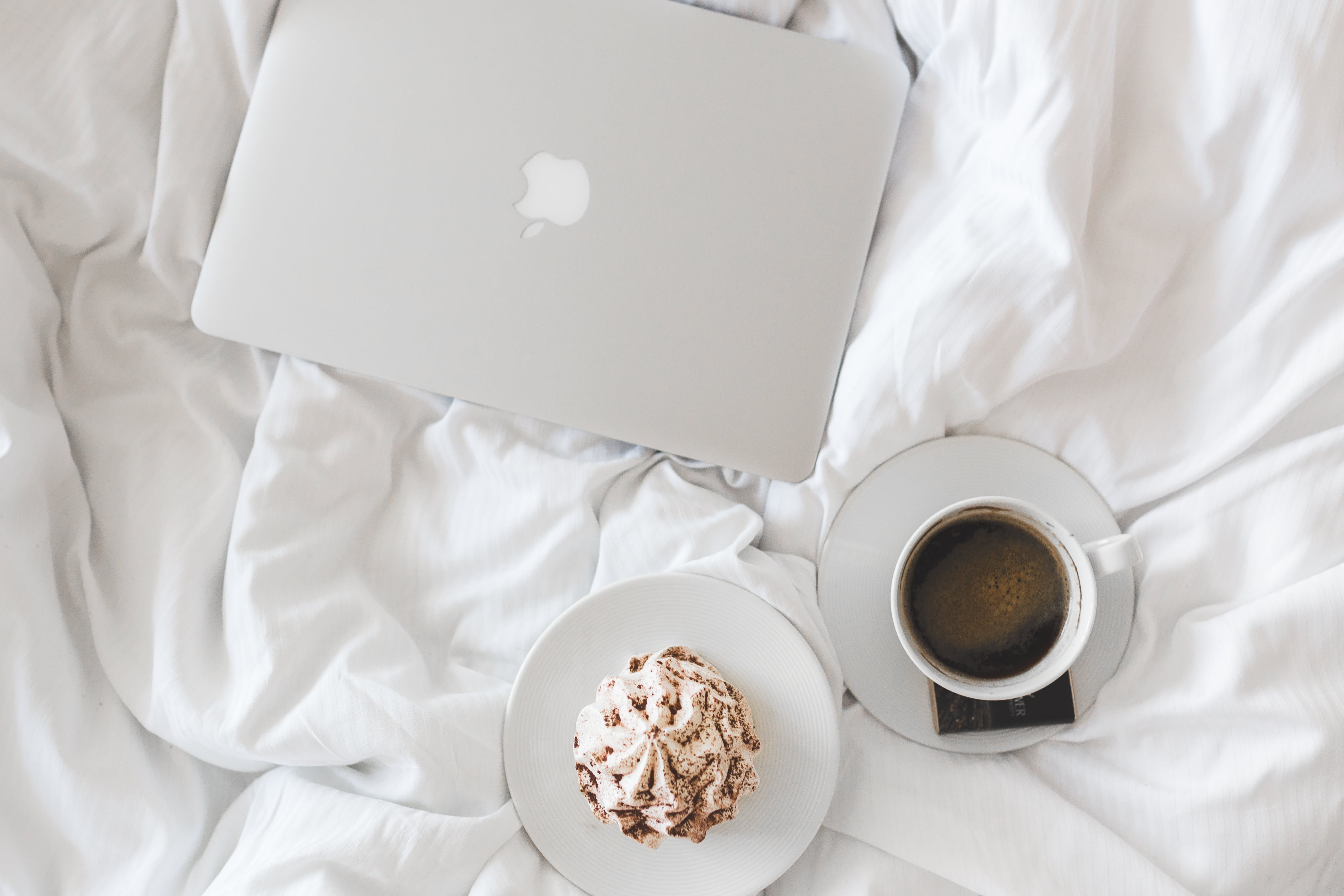 Silver Macbook on White Bed Comforter
