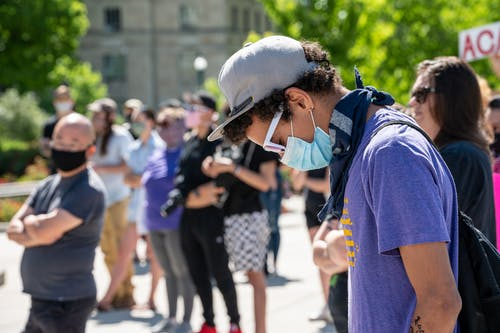 Side view of guy in casual clothes and cap and protective mask standing against crowd at sunny day