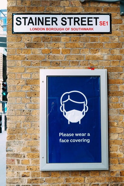 Signboard with reminder to wear face mask on building wall