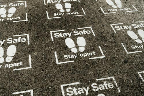 From above white sign of feet and inscription Stay Safe Stay Apart painted on asphalt road during coronavirus outbreak