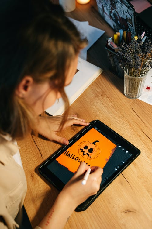 Person Drawing a Jack O'Lantern on a Tablet
