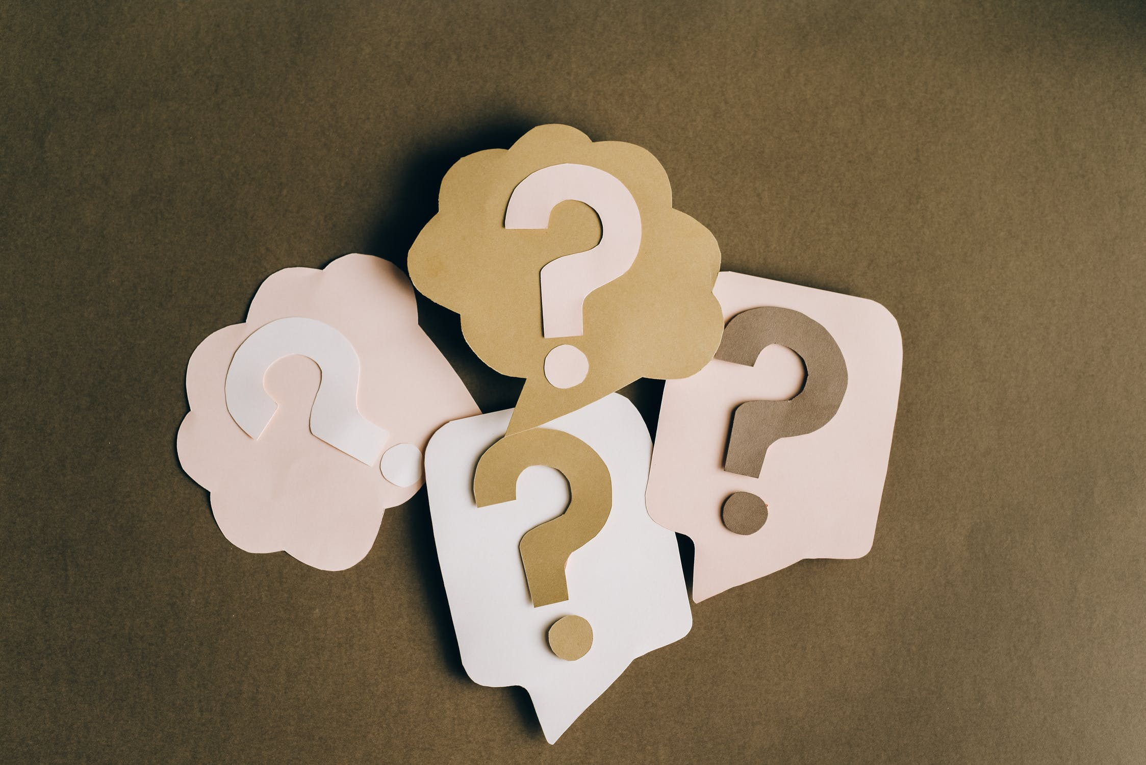 Paper cutouts of question marks in speech bubbles sit on a slate background. Photo used courtesy of Pexels.com
