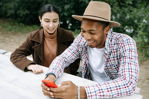 Woman And A Man Sitting On A Bench Using Smartphone