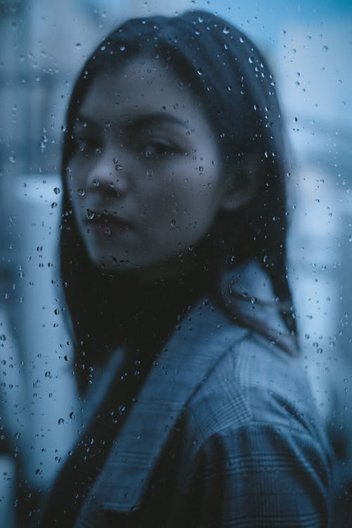 Sad teen looking through window with raindrops