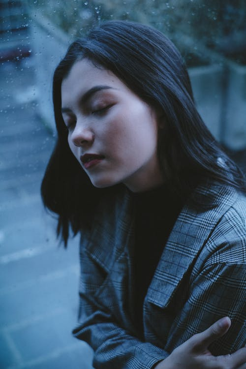 Dreamy teen with eyes closed leaning on wet window