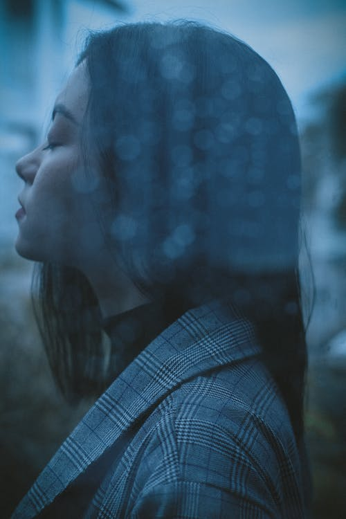 Through glass side view of upset teen girl with closed eyes standing behind wet window in rainy day