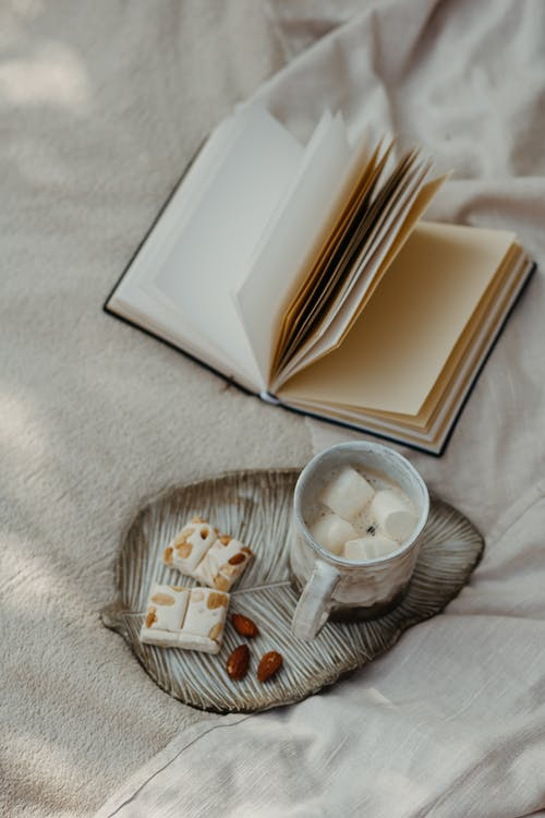 White Book Beside Clear Glass Cup on White Textile