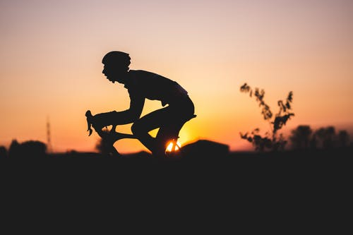 Silhouette of Man Riding on Bicycle during Sunset