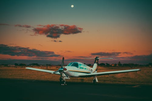 Small airplane on airfield in countryside against sundown sky