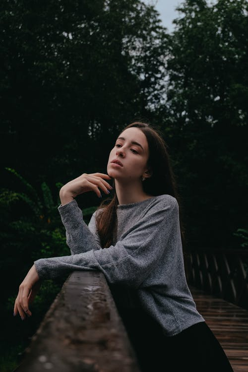 Attractive brown haired female standing on bridge in green forest and leaning on fence while thoughtfully looking down