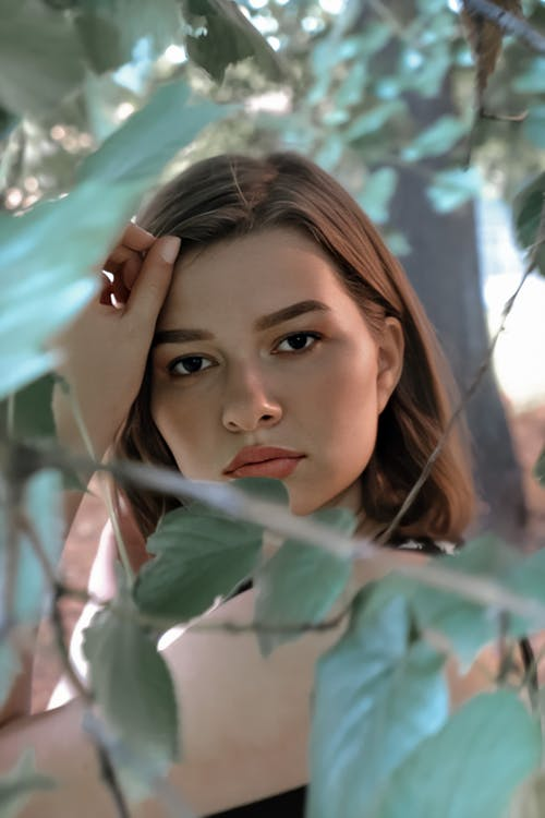 Attractive young woman under green tree