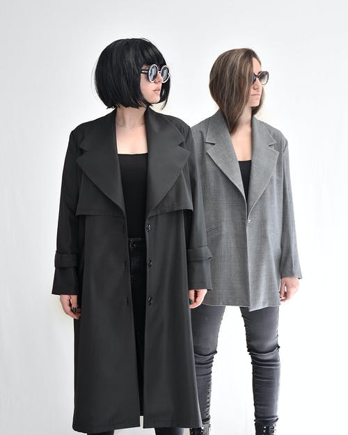 Young stylish women in contemporary clothes and sunglasses standing on white background while looking away