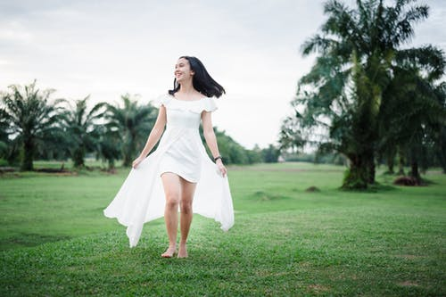 Woman in White Sleeveless Dress Standing on Green Grass Field