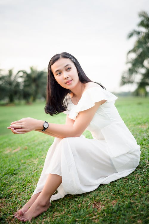 Woman in White Dress Sitting on Green Grass