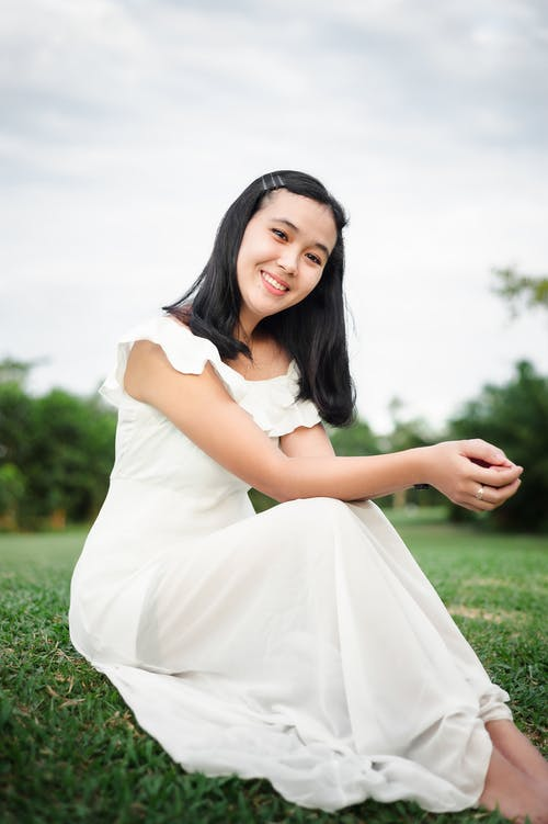 Woman in White Dress Sitting on Green Grass Field
