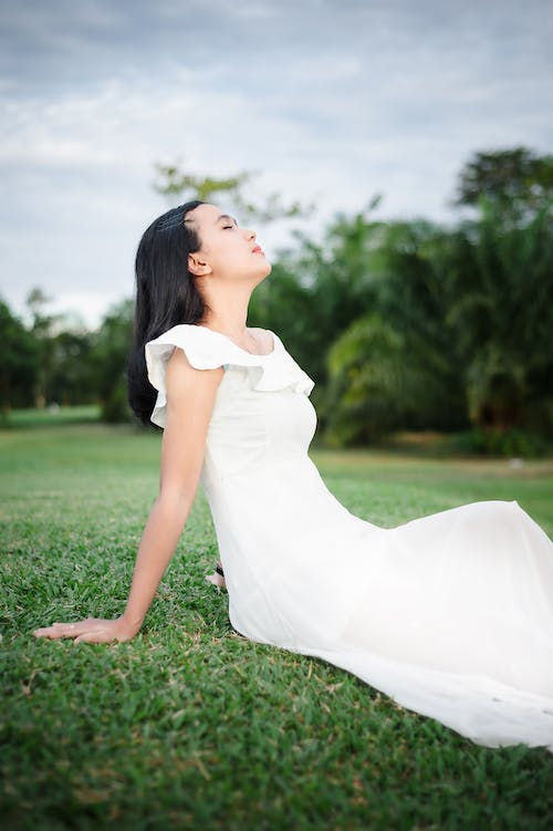 Woman in White Dress Lying on Green Grass Field