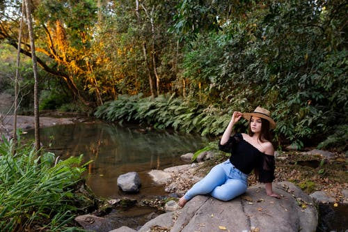 Woman in Black Tank Top and Blue Denim Jeans Sitting on Rock Near River