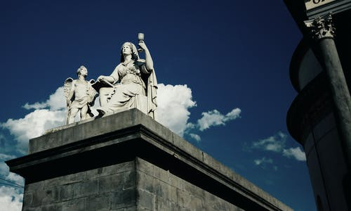 Woman Sitting Beside Cherub Statue