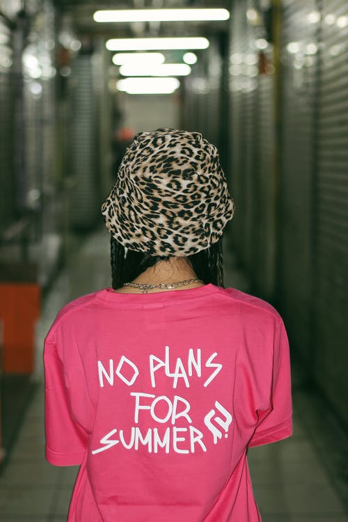 Back view of unrecognizable female teenager in stylish hat and t shirt with No Plans For Summer inscription standing in corridor of modern building