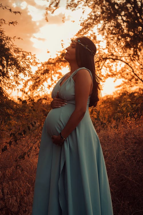 Side view of pregnant female in long dress with wreath on head standing on grassy lawn near branches with hand on belly