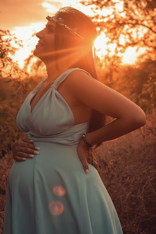 Side view of happy pregnant female standing with hand on back and on belly in nature with sun shining through branches of tree