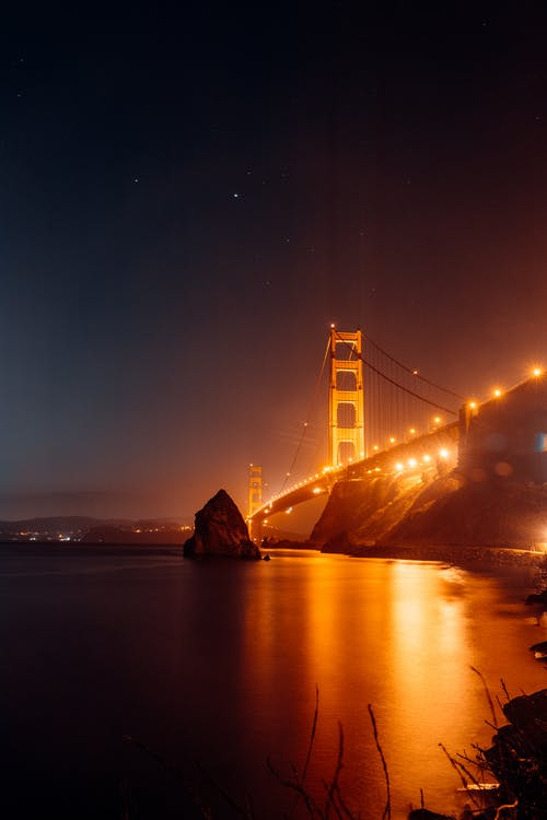 Illuminated Golden Gate Bridge above calm water at night