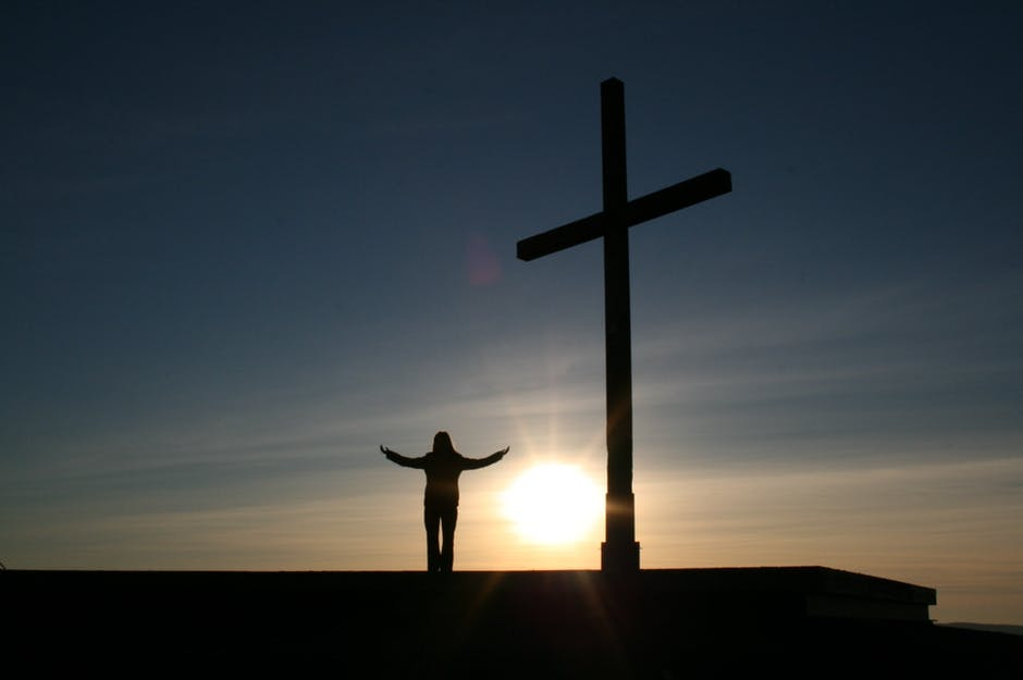 Silhouette of Person Standing Beside Cross during Sunset