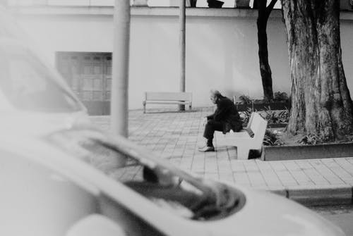 Grayscale Photo of Woman Sitting on Bench