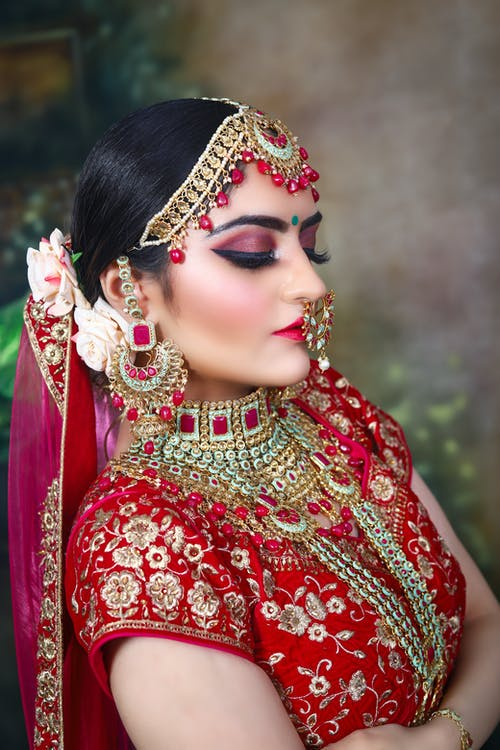 Side view of confident young Indian female in traditional red clothes with necklace and makeup with piercing and headdress with earrings and roses in head with veil and closed eyes