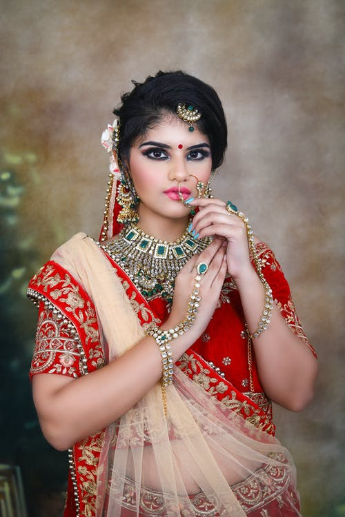 Indian lady wearing traditional bridal clothes with makeup and jewelries