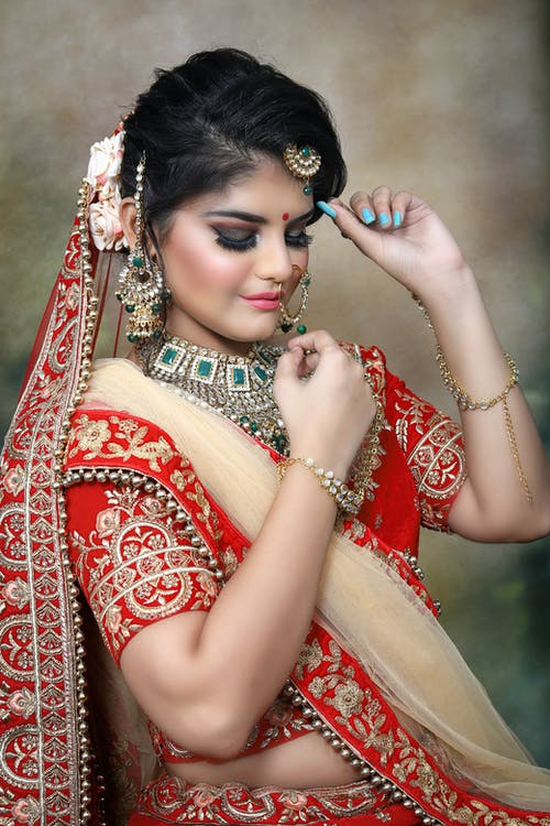 Thoughtful young Indian female in traditional bridal clothes and sari with makeup and big necklace with piercing and earrings with veil and bracelets with closed eyes