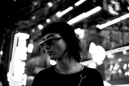 Black and white of serious androgynous Asian man in sunglasses standing on street