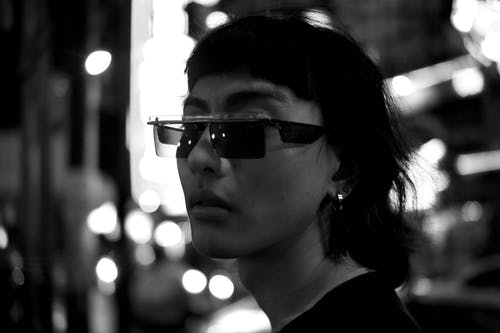 Stylish Asian man in sunglasses standing on street