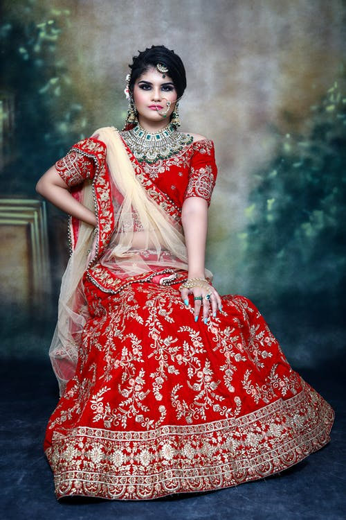 Indian female in traditional bridal clothes with sari and jewelries