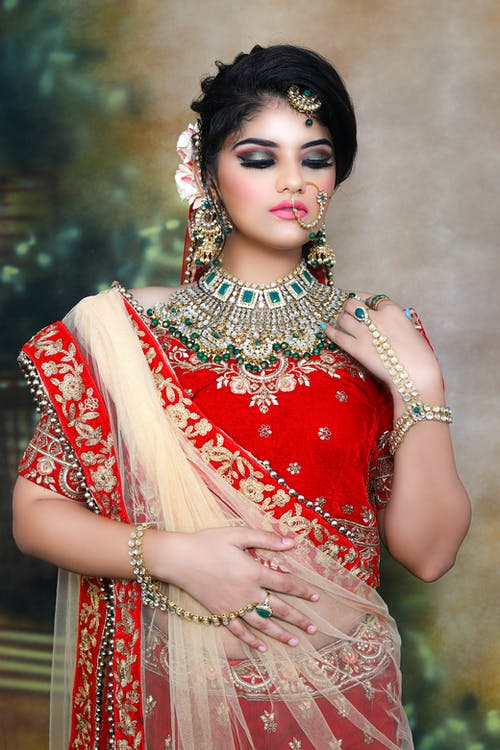 Thoughtful young Indian female in red traditional clothes and sari with makeup and piercing with bracelets and necklace with hairdo with closed eyes