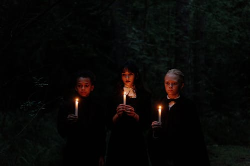 3 Men in Black Robe Holding Lighted Candles