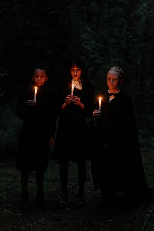 3 Men in Black Robe Holding Lighted Candle