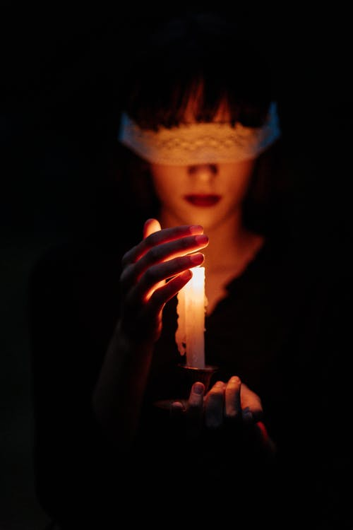 Blindfolded Woman With a Lit Candle