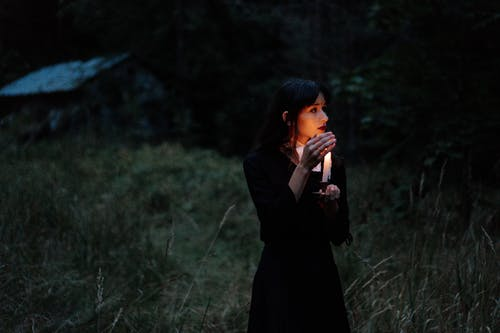 Woman in Black Dress Standing on Green Grass Field