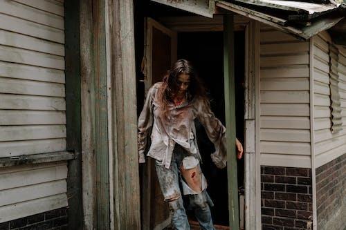 Woman in White Jacket and Blue Denim Jeans Standing Beside Brown Wooden Door