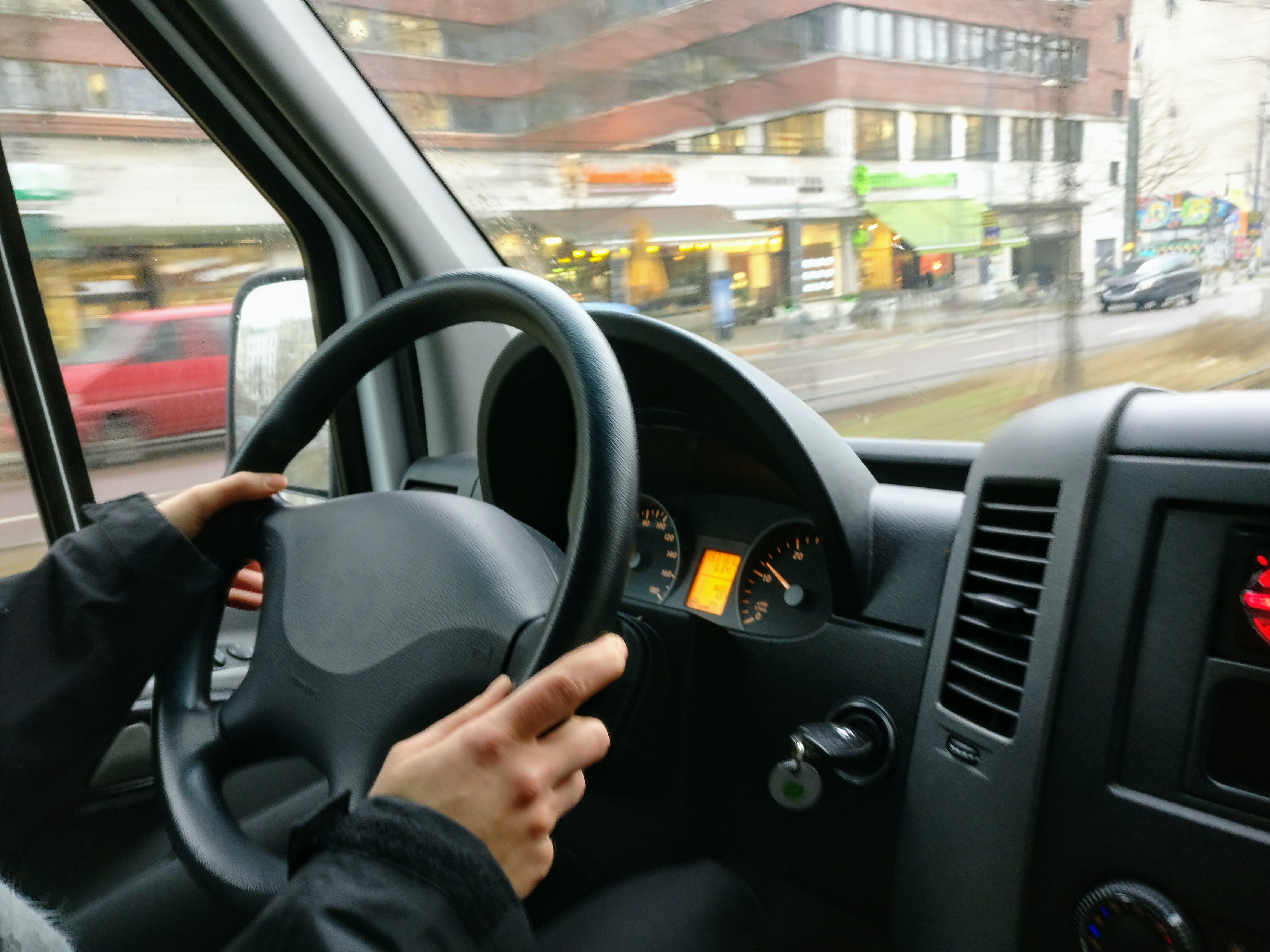 Person Holding Steering Wheel of Car