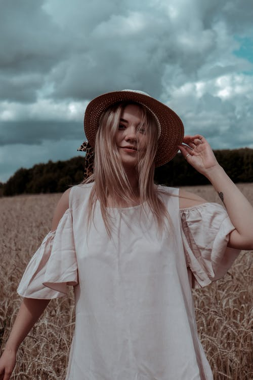 Cheerful female in straw hat and summer dress standing in wheat meadow under cloudy sky and looking at camera