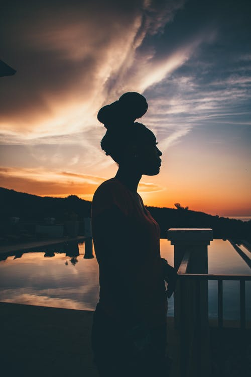 Side view of anonymous black female traveler silhouette contemplating ocean near mount under bright cloudy sky at sundown