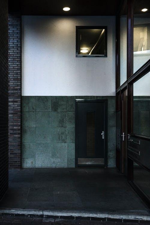 Black Wooden Door Near White Wall