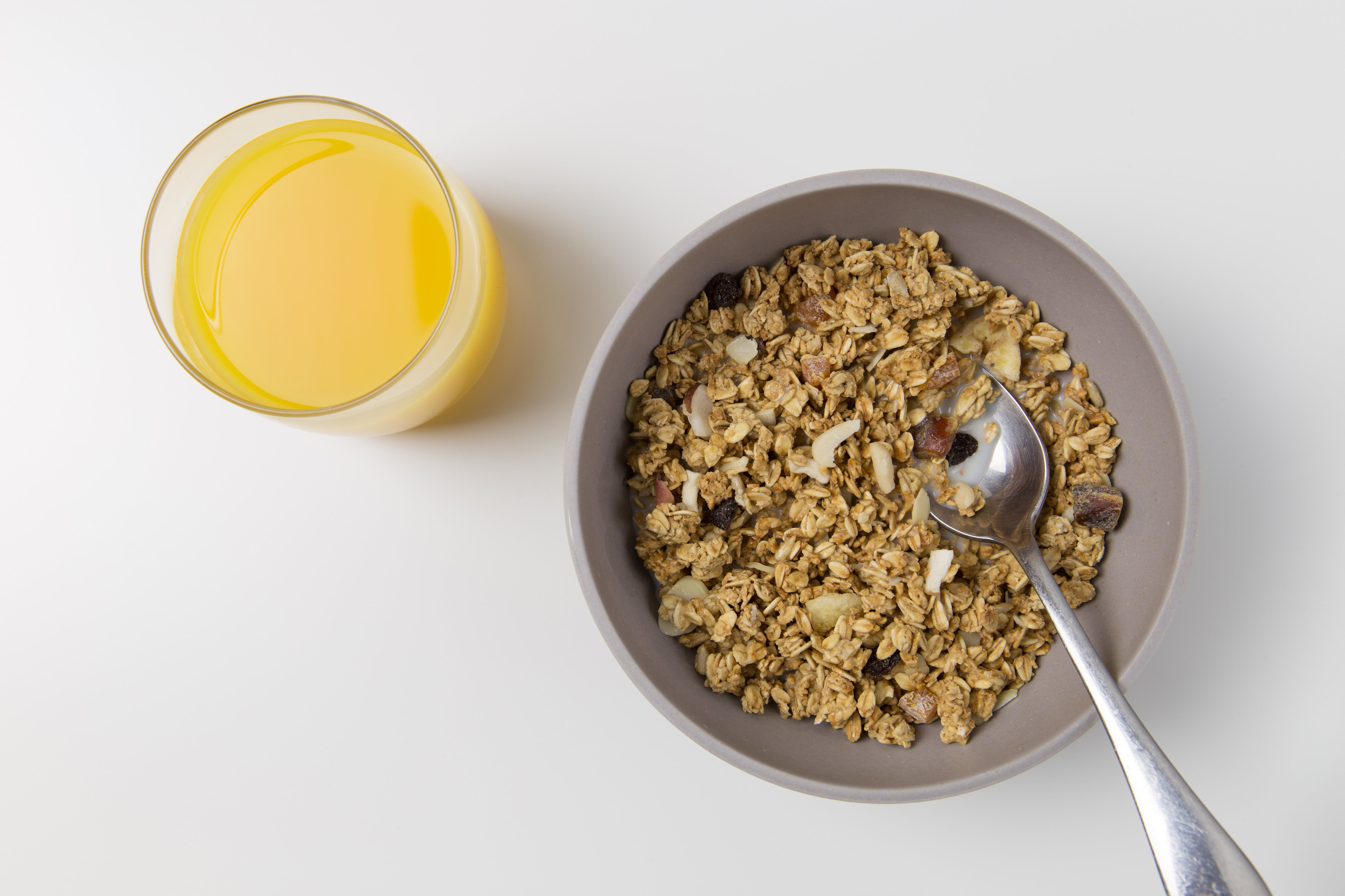 bowl of cereals with fruits and a glass of juice